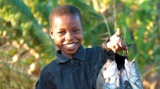 A girl hold an abundance of fish